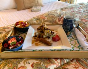 Breakfast tray in bed. On the tray is baked blueberries in a crust, sausage on the side. Fruit bowls and coffee.