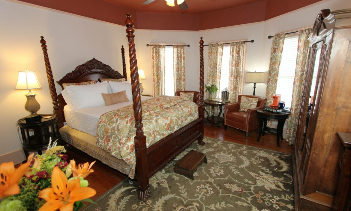 Anastasia room with four poster king bed, bay windows and seating area.