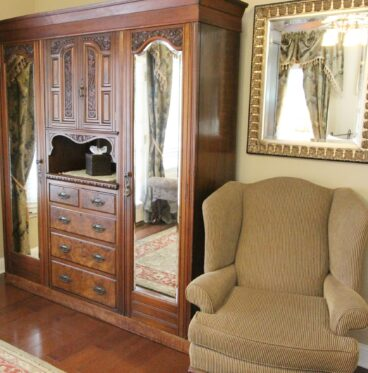 comfortable chair next to armoire