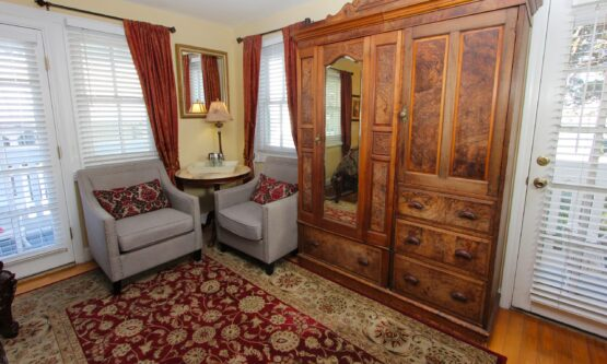 two comfy stuffed chairs and armoire